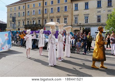 CLUJ-NAPOCA ROMANIA - MAY 27 2017: Young girls dressed as caryatid columns with an entablature on their head march on the streets at the opening parade of the Cluj Days festival.