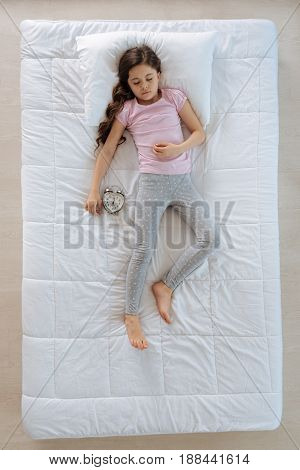 Pleasant relaxation. Peaceful nice cute girl having a nap and enjoying it while lying in her bed near the alarm clock