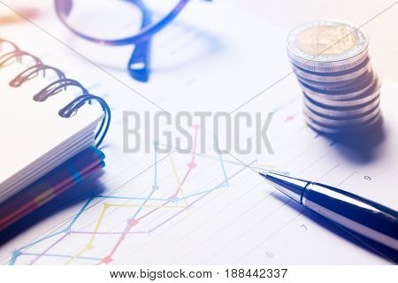 Graph summary report and financial analyzing concept Pen and notebook and eyeglasses on paper report.