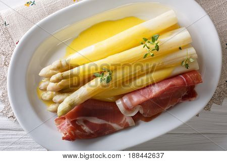 Delicious Fresh White Asparagus With Hollandaise Sauce And Ham Close-up On A Plate. Horizontal Top V