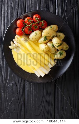 Asparagus Served With Hollandaise Sauce, New Potatoes And Tomatoes Close-up. Vertical Top View