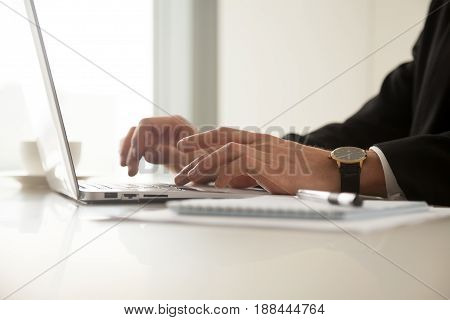 Close up image of guys hands in wristwatch typing on laptop in office. Businessman working on computer at workplace. Office worker browsing internet, communicate online, write blog in social network