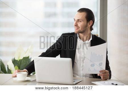 Successful businessman satisfied with good financial statistic in quarterly report. Young entrepreneur at work desk thinking about company perspectives. Executive dreamily looks far away at workplace