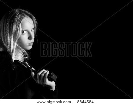 serious girl with gun on black background with copy space, monochrome