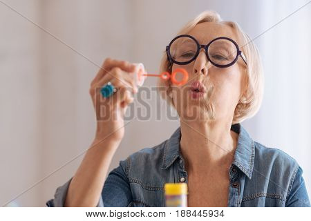 Begin to blow. Funny elderly female wearing round glasses looking at stick with soap while enjoying her age