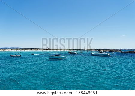Luxury yachts in turquoise beach of Formentera Illetes.