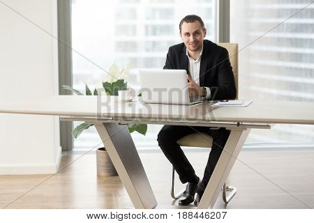 Successful entrepreneur sitting at modern work desk in front of laptop and looking in camera with smile. Company leader working on computer at workplace. Executive manager or CEO ready for cooperation
