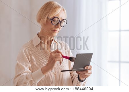 Do not overdo. Serious woman in age wearing round glasses pressing lips while looking downwards