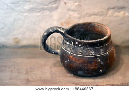 Old clay mug stands on a wooden surface near a white brick wall