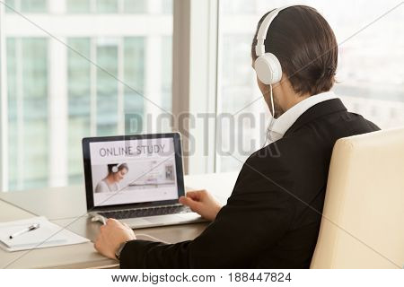 Man in headphones at of laptop with online study service web page on screen. Office worker chooses free online qualification training course, improving work skills in internet. Back view over shoulder