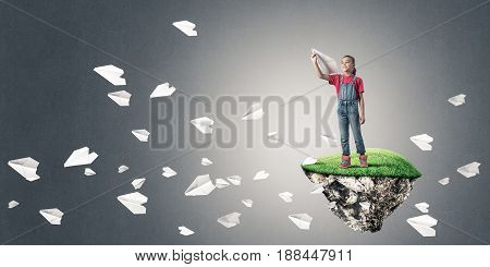 Cute kid girl standing on flying island throwing paper plane