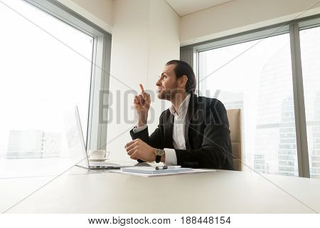 Thoughtful businessman sitting at desk in front of laptop with raised forefinger. Successful entrepreneur ponders decision, thinking with interest about solution at workplace. Manager has a great idea