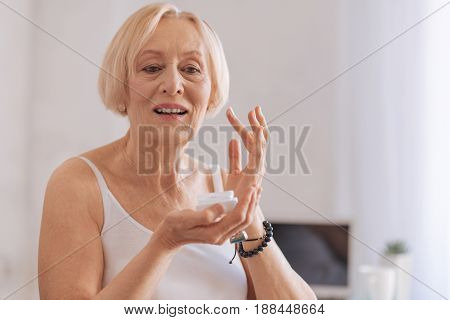 Rejuvenate effect. Elegant woman keeping mouth opened looking downwards while holding care cream in right hand