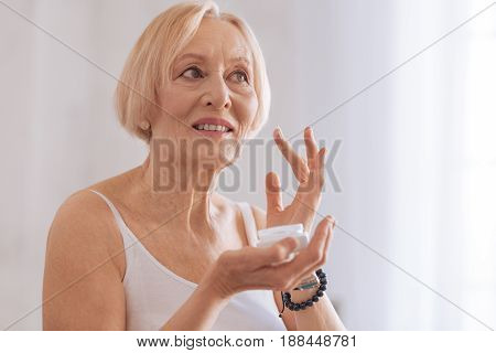 Expensive cream. Enigmatical woman keeping smile on face looking aside while putting cream on cheeks