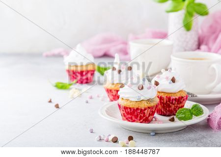 Mini cupcakes with white frosting cream and pink sprinkles on light gray background. Decorated with basil leaves. Party food concept. Copy space.