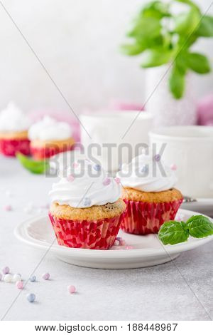Vanilla cupcakes with white frosting cream and pink sprinkles on light gray background. Decorated with basil leaves. Party food concept.