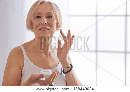 Enjoy your life. Mature woman looking straight at camera keeping smile on face while raising fingers with cream