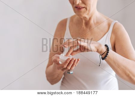 Hope for good result. Attentive mature female person wearing white top putting fingers into cream while keeping smile on face