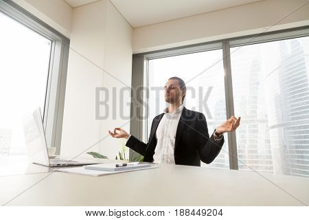 Young man meditating at laptop desk in office. Successful businessman doing yoga exercises at workplace for relaxing and recovery. Executive visualizes in mind positive result with spiritual practices