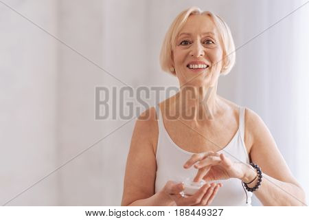Friendly smile. Delighted female person keeping smile on her face looking straight at camera while testing new cream