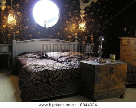 Photograph of a very classy and extraordinary master bedroom designed according feng shui guidelines with a circular window
