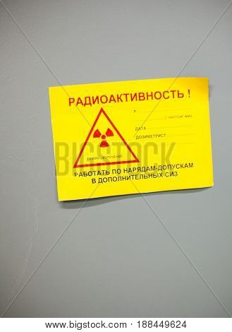 CHERNOBYL UKRAINE - OCTOBER 16 2015: Yellow paper with radiation trefoil symbol warning that workers must have warrant for work and wear additional personal protective equipment. Inscriptions in Russian. Chernobyl Nuclear Power Plant.