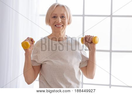 Repeat after me. Healthy elderly woman keeping smile on her face looking straight at camera while holding arms bent in elbows