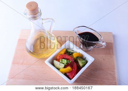 fresh vegetable salad with tomato, cucumber, bell pepper, lettuce leaf in white bowl, olive oil and balsamic souce in bottle. Selective focus
