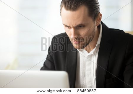 Focused businessman looking on laptop screen. Serious financier reviewing financial market fluctuations. Entrepreneur immersed in work on computer. Young man concentrated on task completing, close up