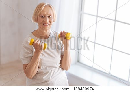 Sporty mood. Attractive female person lifting dumbbells and keeping smile on face while looking straight at camera