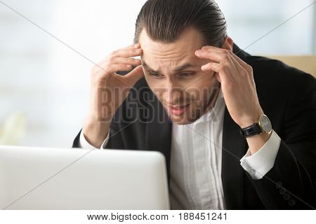 Businessman shocked with fall of company stocks. Stressed entrepreneur with head in hands looking on laptop screen with panic. Young man in despair because of bad news, notice of dismissal, loan debt poster