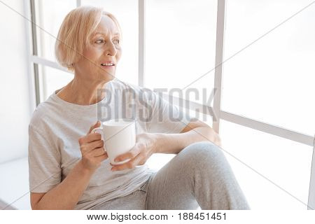 Lets think. Enigmatical elderly female opening her mouth while looking through the window, leaning elbow on left knee
