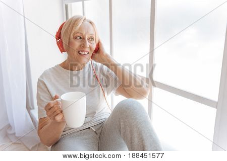 Listen to active music. Pretty smiling woman holding cup in right hand, sitting on the windowsill while looking aside