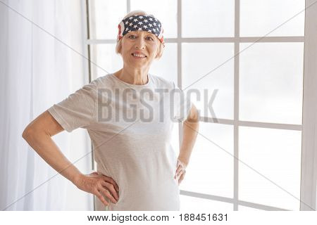 Stylish retirement. Positive female person putting hands on the belt keeping smile on face while posing on camera