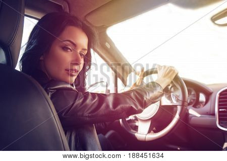 Beautiful brunette woman steers a car an expensive car. Confident and beautiful. Rear view of attractive young woman in casual wear looking over her shoulder while driving a car