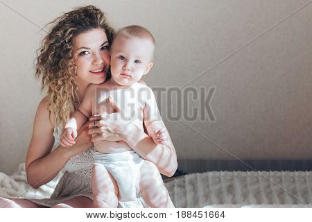 Mother hugging serious baby boy in white dress and baby in pants