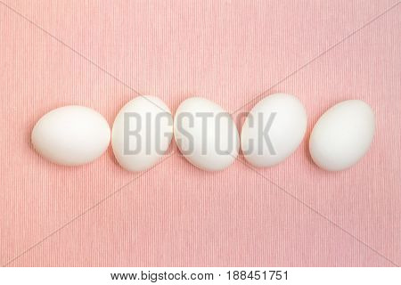 Top view of five white egg isolated on the pink background. Design, visual art, minimalism