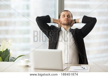 Tired businessman sitting at work desk with laptop, resting with hands behind head. Office worker relaxing at workplace after finishing project on computer. Calm man enjoys good work done, takes break