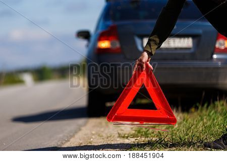 Red warning triangle on road background of car. Focus on road sign