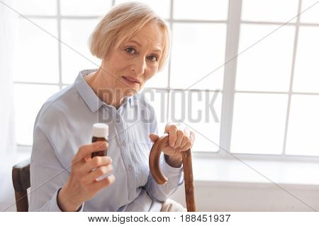 Take medicine. Serious woman opening her mouth keeping bottle with pills in right hand while bowing her head