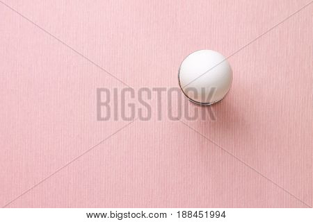 Top view of white egg in egg cup on pink background isolated. Design, visual art, minimalism