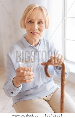 Low angle photo. Mature lady wrinkling her forehead sitting in semi position while holding walking stick in left hand