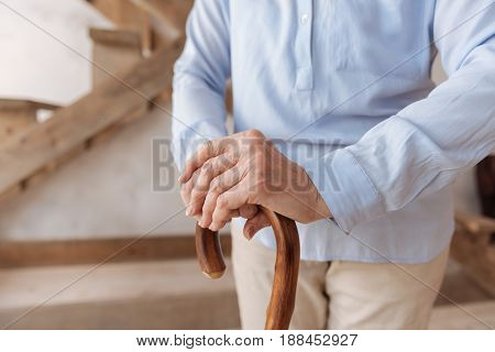 Home sweet home. Old woman having rest while leaning on walking stick and holding hands together