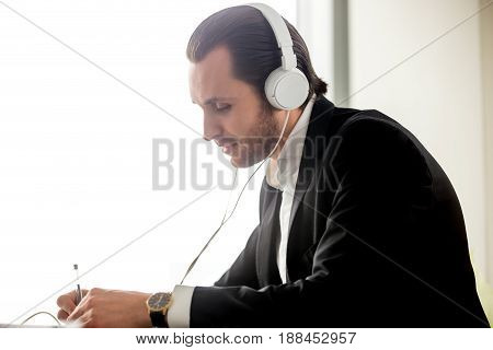Businessman in headphones takes part in online meeting, conference. Young man learning foreign language, listening live stream. Entrepreneur works with enthusiasm and listens favorite music in office