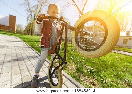 Boy on road in park with balane bike in afternoon. Sunflare