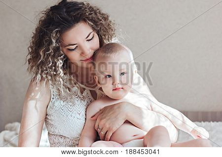 Portrait of adorable blond blue-eyed baby boy looking at the camera with happy smile sitting on his mother's laps in pajamas. Young beautiful woman spending morning with her 10-months old son