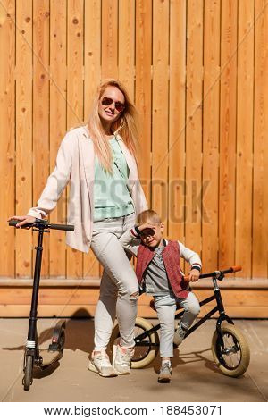 Woman with boy with bicycles near wooden wall in park