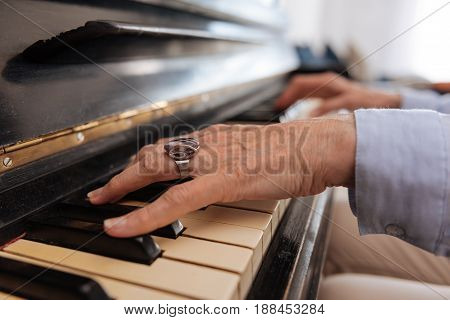 Vintage ring. Old female person wearing blue shirt, having relax while making music