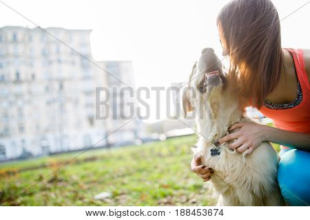 Photo of brunette with labrador dog on lawn at background of houses