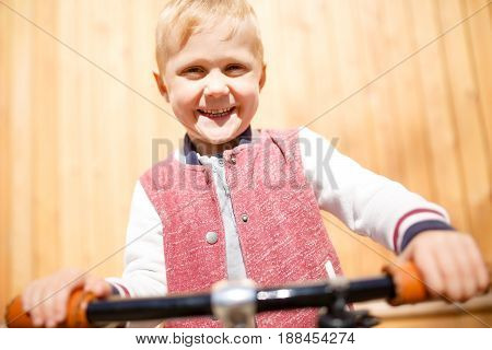 Photo of boy with bicycle near wooden wall